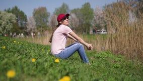La riuscita donna di affari gode del suo tempo libero di svago in un parco con i ciliegi sboccianti di sakura che portano i jeans video d archivio