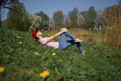 La riuscita donna di affari gode del suo tempo libero di svago in un parco con i ciliegi sboccianti di sakura che portano i jeans immagini stock