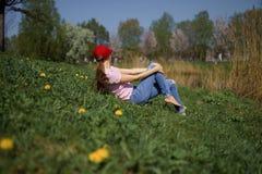La riuscita donna di affari gode del suo tempo libero di svago in un parco con i ciliegi sboccianti di sakura che portano i jeans immagine stock