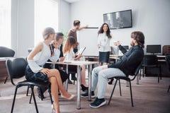 La riuscita gente di affari è parlante e sorridente durante nell'ufficio fotografie stock libere da diritti
