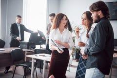 La riuscita gente di affari è parlante e sorridente durante nell'ufficio immagine stock libera da diritti