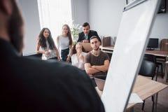 La riuscita gente di affari è parlante e sorridente durante nell'ufficio immagine stock