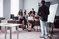 La riuscita gente di affari è parlante e sorridente durante nell'ufficio immagini stock