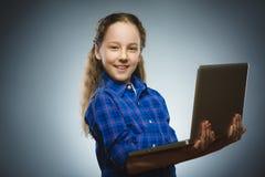 La riuscita ragazza felice che per mezzo del computer portatile ha isolato il fondo grigio Fotografie Stock