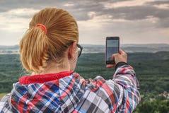 La riuscita viandante femminile prende la foto al bordo immagine stock