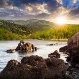 La riva del lago con le pietre si avvicina alla foresta sulla montagna al tramonto Immagine Stock