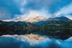 La riva del lago della montagna con chiara chiara acqua blu incredibile, nelle nuvole leggere delle montagne, i picchi è accesa d Fotografie Stock