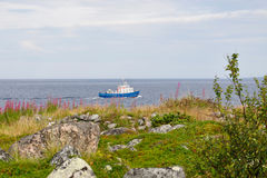 La riva del mar Bianco e una piccola barca blu sull'isola di Bolshoi dell'arcipelago di Zayatsky Solovetsky Fotografia Stock Libera da Diritti