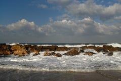 La riva dell'oceano, delle onde e della schiuma di colore bianco fra le pietre costiere rosse Immagini Stock Libere da Diritti