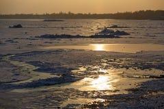 La riva di un mare congelato nell'inverno, collinette del ghiaccio al tramonto Paesaggio del mare di Azov nell'inverno immagini stock