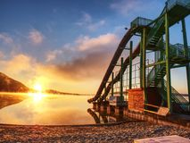 La riva ed il toboggan del tramonto fa scorrere nel lago, Alta torre della scala con lo scivolamento della pista Fotografia Stock