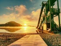 La riva ed il toboggan del tramonto fa scorrere nel lago, Alta torre della scala con lo scivolamento della pista Fotografie Stock