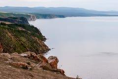 La riva rocciosa del lago Baikal con le pietre di sporgenza e del muschio rosso su loro immagini stock