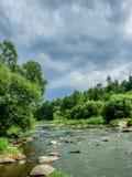 La rivière avec de grandes pierres et ciel foncé dans la forêt photo libre de droits