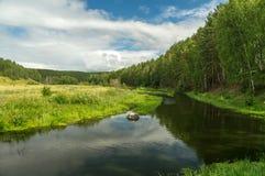 La rivière avec un pré et bois pendant l'été Photo libre de droits