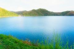 La rivière bleue, la colline verte et le champ d'herbe verte près du SI Photographie stock libre de droits