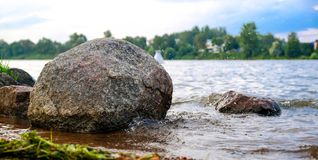 La rivière claire avec des roches mène vers des montagnes allumées par coucher du soleil photos stock
