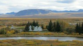 La rivière d'Oxara en parc national islandais Thingvellir dans le jour d'automne, bâtiments sont sur le rivage banque de vidéos