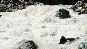 La rivière de montagne sort de dessous le glacier, un courant d'eau puissant est cassée sur le plan rapproché de roches, mouvemen banque de vidéos