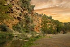 La rivière et sauter de la jeune mariée dans des couteaux au coucher du soleil Photos stock