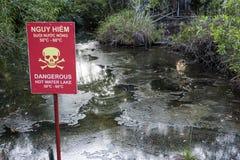 La rivière naturelle de Hot Springs et un avertissement vietnamien anglais bilingue panneau dans Bình Chau, Vietnam images stock