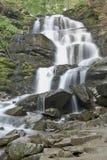La rivière pure et froide de montagne fonctionne entre les pierres rocheuses et coule dans la cascade Image libre de droits
