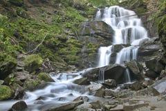 La rivière pure et froide de montagne fonctionne entre les pierres rocheuses et coule dans la cascade Photo stock