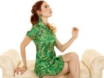 La robe asiatique de femme principale rouge se reposent sur le sofa recherchent Photographie stock libre de droits