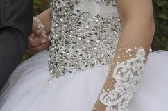 La robe blanche de jeune mariée avec des perles est une partie du corps Photos stock