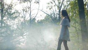 La robe blanche de port de femme mystérieuse marche dans le brouillard de brume dans les bois au lever de soleil - banque de vidéos