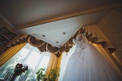 La robe de mariage accroche à une fenêtre 1722 Photos libres de droits