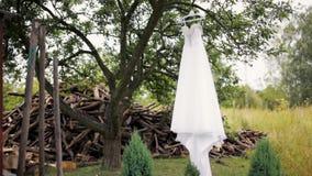 La robe l'épousant blanche avec des fausses pierres accroche sur un arbre près de la pile du bois de chauffage banque de vidéos