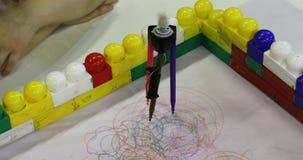 la Robot-bussola sta disegnando i cerchi con i pennarelli colorati video d archivio