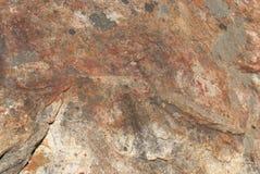 La roca de Brown con rojo mancha el fondo o la textura Imagenes de archivo