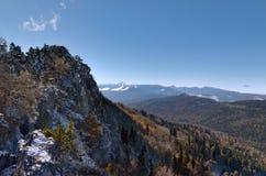 La roca en las montañas al bosque del pino al horizonte Foto de archivo
