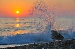 La roca que se estrella de la onda crea puesta del sol del remolino del agua Foto de archivo libre de regalías