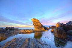 La roccia della guarnizione di pelliccia dalla bella spiaggia illuminata dai primi raggi del sole di mattina alla costa nordica d immagine stock