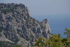 La roccia grigia e alta nella priorità alta riguarda la superficie blu dell'acqua di mare Immagini Stock
