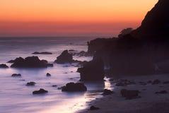 La roccia ha coperto la spiaggia della California al tramonto Fotografie Stock