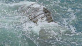 La roccia sola lavata dall'irrompere spumoso delle onde del mare spruzza, potere della natura archivi video