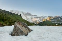 La roche émerge de la neige dans le pré alpin Photographie stock libre de droits