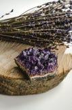 La roche crue d'améthyste avec le groupe de lavande aromatique fleurit sur ésotérique rustique en bois naturel Photo stock