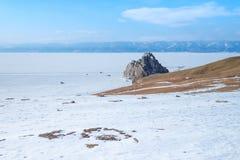 La roche de chaman s'est prolongée au lac congelé et à la terre neigeuse du village de Khuzhir sur l'île d'Olkhon photographie stock