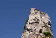 La roche de Steeple avec les grimpeurs en travers essayant la portée font une pointe Image libre de droits