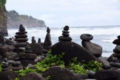 La roche empile l'équilibrage sur la plage de sable de noir de Polulu image libre de droits