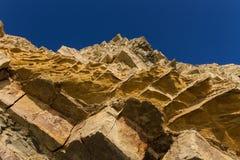 La roche jaune et orange de Sandy sur un bzckground profond de ciel bleu Photographie stock
