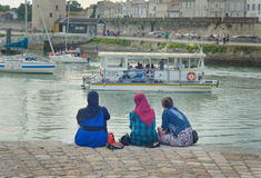 LA ROCHELLE, FRANCE - AUGUST 12, 2015: Muslim woman wearing hijab looking on the ocean Atlantic and yachts. LA ROCHELLE, FRANCE - AUGUST 12, 2015: Muslim woman royalty free stock image