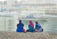 LA ROCHELLE, FRANKREICH - 12. AUGUST 2015: Moslemische Frau tragendes hijab, das auf dem Ozean und den Yachten La Rochelle, Frank lizenzfreie stockfotografie