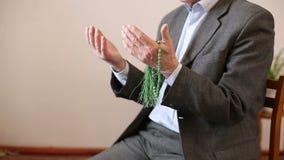 La rogación de las manos de un viejo hombre con el rosario gotea