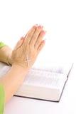 La rogación entrega la biblia con la cruz del rhinestone Imagen de archivo